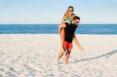 Los pares alegres jovenes felices juntos durante vacaciones de verano vacation en la playa tropical Fotos de archivo libres de regalías