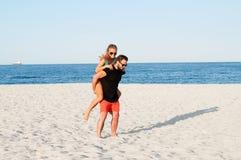 Los pares alegres jovenes felices juntos durante vacaciones de verano vacation en la playa tropical Imagen de archivo