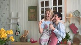 Los pares alegres jovenes se divierten que baila y que canta mientras que cocinan en la cocina en casa almacen de video
