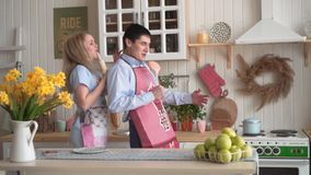 Los pares alegres jovenes se divierten que baila y que canta mientras que cocinan en la cocina en casa almacen de metraje de vídeo