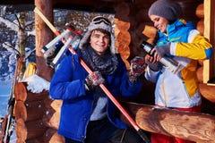Los pares alegres pasan vacaciones de invierno en la cabaña de la montaña fotos de archivo libres de regalías