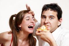 Los pares alegres que comen una pizza Foto de archivo libre de regalías