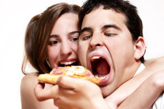 Los pares alegres que comen una pizza Imagen de archivo