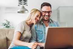 Los pares alegres se relajan y trabajan en el ordenador portátil en la sala de estar moderna imagenes de archivo