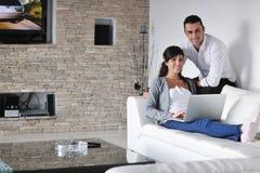 Los pares alegres se relajan y trabajan en la computadora portátil en el país fotos de archivo libres de regalías