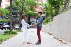 Los pares asiáticos celebran la sonrisa feliz de las manos que mira a Fotos de archivo libres de regalías