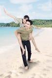 Los pares asiáticos disfrutan de luna de miel en la playa foto de archivo