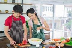 Los pares asiáticos en delantal, hacen cocinar juntos El hombre se est? preparando para cortar verduras con los cuchillos Ali?o d fotografía de archivo