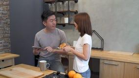 Los pares asiáticos felices hermosos se están alimentando en la cocina Hombre que usa la tableta y bebiendo una taza de café almacen de video