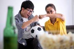 Los pares asiáticos jovenes aman el mirar del partido de fútbol en la TV y animar Fotografía de archivo