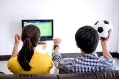 Los pares asiáticos jovenes aman el mirar del partido de fútbol en la TV y animar Foto de archivo libre de regalías
