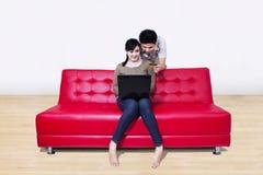 Los pares asiáticos pagan en línea usando tarjeta de crédito en casa Fotos de archivo