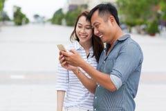 Los pares asiáticos usando mensaje de teléfono elegante de la célula sonríen Imagen de archivo