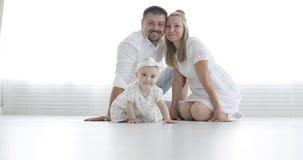 Los pares atractivos jovenes y el bebé lindo se sientan en el piso blanco y miran la cámara almacen de video