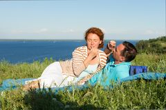 Los pares atractivos tienen un resto en la hierba cerca del lago grande Pares cariñosos en día de verano pares de mentira felices imagen de archivo