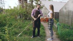 Los pares atractivos trabajan cerca de invernadero El jardinero del hombre en delantal recoge la basura en jardín mientras que su almacen de video