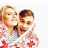 Los pares bastante adolescentes de los jóvenes en la Navidad miden el tiempo de calentarse en diciembre rojo Fotografía de archivo