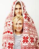 Los pares bastante adolescentes de los jóvenes en la Navidad miden el tiempo de calentarse en la manta adornada roja, individuo d Fotografía de archivo libre de regalías