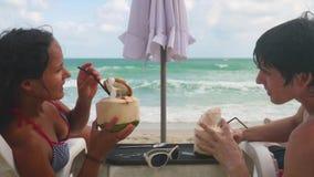 Los pares bonitos jovenes que se relajan en sunbeds beben los cócteles del coco en centro turístico exótico en la playa de Koh Sa almacen de metraje de vídeo