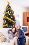 Los pares cariñosos acercan al árbol de navidad Imagen de archivo libre de regalías