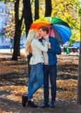 Los pares cariñosos el fecha debajo del paraguas que se besa en caída parquean imagen de archivo libre de regalías