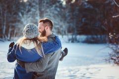 Los pares cariñosos felices que caminan en el bosque nevoso del invierno, pasando la Navidad vacation juntos Imagen de archivo libre de regalías