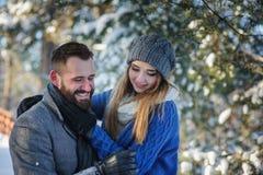 Los pares cariñosos felices que caminan en el bosque nevoso del invierno, pasando la Navidad vacation juntos Fotografía de archivo libre de regalías