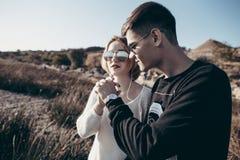 Los pares cariñosos jovenes de adolescentes en gafas de sol sostienen las manos y el li Foto de archivo