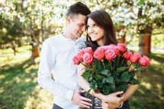 Los pares cariñosos jovenes en amor, la muchacha que sostiene las flores, felices y disfrutan de la naturaleza, de la publicidad, Foto de archivo libre de regalías
