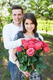 Los pares cariñosos jovenes en amor, la muchacha que sostiene las flores, felices y disfrutan de la naturaleza, de la publicidad, Imágenes de archivo libres de regalías