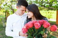 Los pares cariñosos jovenes en amor, la muchacha que sostiene las flores, felices y disfrutan de la naturaleza, de la publicidad, Fotografía de archivo libre de regalías