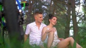 Los pares cariñosos jovenes tienen un basar en la hierba después de completar un ciclo en bosque del pino almacen de video