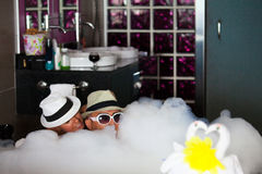 Los pares cariñosos mienten en un cuarto de baño con baño-espuma. Fotografía de archivo