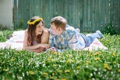 Los pares cariñosos en la primavera cultivan un huerto en una manta de la comida campestre para mentir Foto de archivo libre de regalías