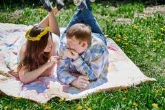 Los pares cariñosos en la primavera cultivan un huerto en una manta de la comida campestre para mentir Fotos de archivo libres de regalías