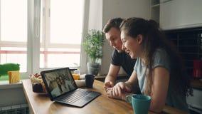 Los pares caucásicos agradables jovenes que se sentaban en la tabla delante del ordenador portátil skyping con su positivo feliz  almacen de metraje de vídeo