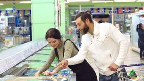 Los pares caucásicos lindos eligen las comidas congeladas del refrigerador del supermercado almacen de video