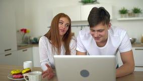 Los pares caucásicos sirven y la mujer está utilizando el ordenador en la cocina Concepto del hogar, de la tecnología y de las re metrajes
