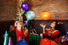 Los pares celebran a la fiesta de Navidad con el globo Fotos de archivo libres de regalías