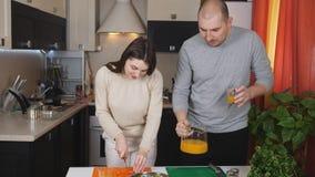 Los pares cocinaron la cena juntos La esposa corta las verduras para una ensalada, y mi marido vierte los vidrios de zumo de nara almacen de video