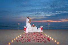 Los pares comparten una cena romántica con las velas Foto de archivo