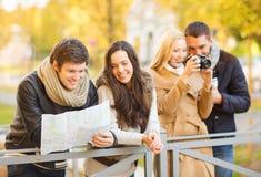 Los pares con el mapa y la cámara turísticos en otoño parquean Imagenes de archivo