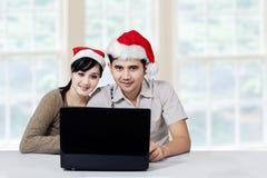 Los pares con el ordenador portátil disfrutan de día de fiesta de la Navidad Foto de archivo