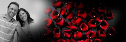 Los pares con el ` s de la tarjeta del día de San Valentín aman los pétalos color de rosa de la transición Fotografía de archivo libre de regalías