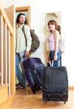 Los pares con las maletas acercan a la puerta en casa Fotografía de archivo libre de regalías