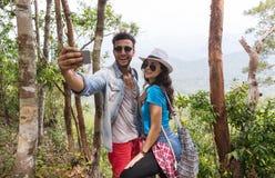 Los pares con las mochilas toman la foto de Selfie sobre el senderismo del paisaje de la montaña, el hombre joven y la mujer en t imagen de archivo libre de regalías