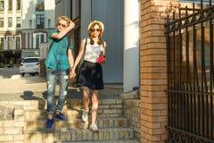 Los pares de adolescentes est?n caminando a trav?s de las calles de la ciudad, llevando a cabo las manos fotografía de archivo