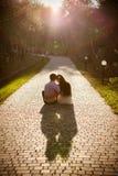Los pares de adolescentes se sientan en calle juntos Imagen de archivo