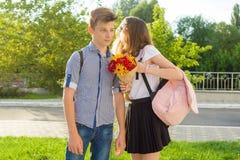 Los pares de los adolescentes son que caminan, riendo, hablando, muchacha con el ramo de flores Fotografía de archivo