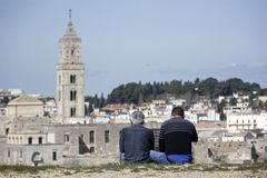 Los pares de amigos comtemplan la ciudad de Matera de las alturas en fron Imágenes de archivo libres de regalías